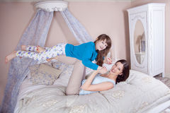 Happy mother and daughter lay in bed and having fun. Royalty Free Stock Image