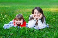 Happy mother and daughter lie on the grass in the park Stock Photos