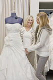 Happy mother and daughter looking at beautiful wedding dress in bridal store Royalty Free Stock Photography