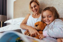 Happy mother and daughter on bed reading book royalty free stock photo