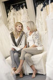 Happy mother and daughter looking at each other while sitting on sofa in bridal boutique Stock Images