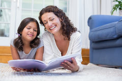 Happy mother and daughter lying on the floor and reading a book Royalty Free Stock Images