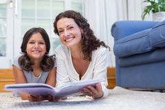 Happy mother and daughter lying on the floor and reading a book Stock Photos