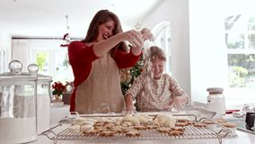Happy mother and daughter making cookies for christmas eve. Smiling young woman with little girl sprinkling flour on dough. Mother and daughter preparing stock video footage
