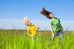 Happy mother and daughter making exercises. On field. Against the backdrop of blue sky Stock Image
