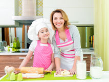 Happy mother and daughter making pies. Stock Images