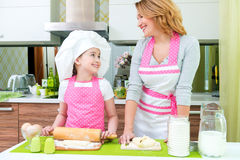 Happy mother and daughter making pies. Royalty Free Stock Photos