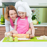 Happy mother and daughter making pies. Royalty Free Stock Photo