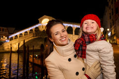 Happy mother and daughter near Rialto Bridge in Christmas Venice Royalty Free Stock Photo