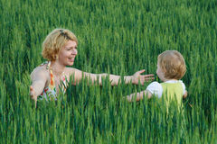 Happy mother and daughter open arms on a wheat field Royalty Free Stock Photos