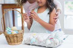 Happy mother and daughter painting easter eggs Royalty Free Stock Images