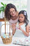 Happy mother and daughter painting easter eggs Royalty Free Stock Image