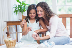 Happy mother and daughter painting easter eggs Stock Image