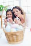 Happy mother and daughter painting easter eggs Stock Photography
