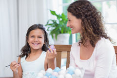 Happy mother and daughter painting easter eggs Stock Photo