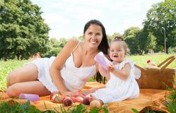 Happy mother with daughter in the park picnicking Stock Image