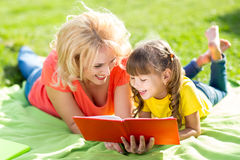 Happy mother with daughter in park reading book Royalty Free Stock Photos