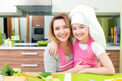 Happy mother and daughter in pink apron. Stock Photos