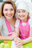 Happy mother and daughter in pink apron. Portrait of happy smiling mother and daughter in pink apron at the kitchen stock images