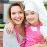 Happy mother and daughter in pink apron. Portrait of happy smiling mother and daughter in pink apron at the kitchen stock photo
