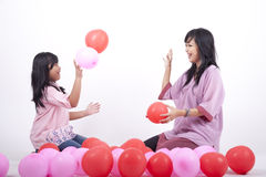 Happy Mother and Daughter play with balloon. Mother and daughter having a guality time together Stock Photos