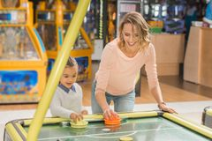 happy mother and daughter playing air hockey together
