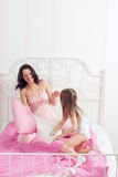 Happy mother and daughter playing in bad Stock Photography