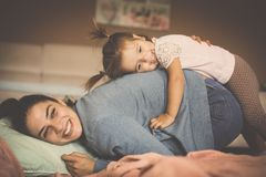 Mother and daughter playing on floor at home together. stock photo