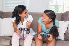 Happy mother and daughter playing video games together on sofa Stock Image