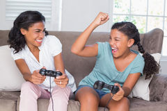 Happy mother and daughter playing video games together on sofa Stock Photo