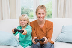 Happy mother and daughter playing video games together on sofa Royalty Free Stock Image