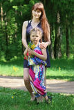 Happy mother and daughter pose with flowers in forest Royalty Free Stock Images
