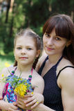 Happy mother and daughter pose with flowers Royalty Free Stock Photography