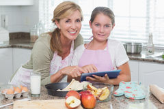 Happy mother and daughter preparing cake together Stock Photos