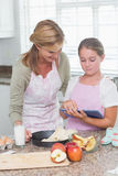 Happy mother and daughter preparing cake together with tablet Stock Photo