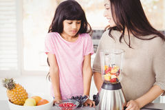 Happy mother and daughter preparing fruit juice Stock Photography