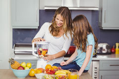 Happy mother and daughter preparing fruit juice Stock Photos