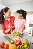 Happy mother and daughter preparing salad Royalty Free Stock Image