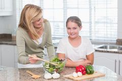 Happy mother and daughter preparing salad together Royalty Free Stock Image