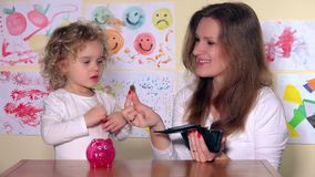 Happy mother and daughter putting coins into piggy bank. Static shot. 4K UHD stock footage