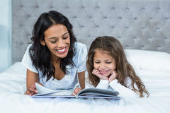 Happy mother and daughter reading a book on the bed Royalty Free Stock Photos
