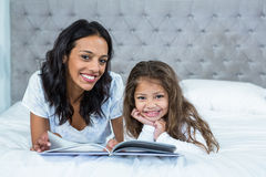 Happy mother and daughter reading a book on the bed Royalty Free Stock Photography