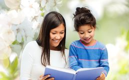 Happy mother and daughter reading book Royalty Free Stock Photos