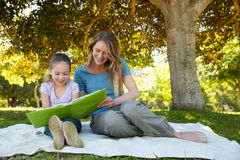 Happy mother and daughter reading a book at park Royalty Free Stock Image