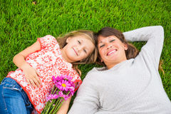 Happy mother and daughter relaxing outside on green grass. Spend Stock Photo