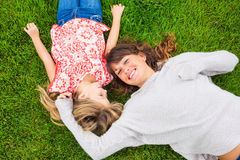 Happy mother and daughter relaxing outside on green grass. Spend Royalty Free Stock Photo