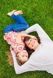 Happy mother and daughter relaxing outside on green grass. Spend Stock Image