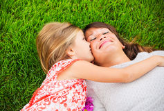 Happy mother and daughter relaxing outside on green grass. Spend Royalty Free Stock Photography