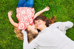 Happy mother and daughter relaxing outside on green grass. Spend Stock Images