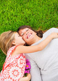 Happy mother and daughter relaxing outside on green grass. Spend Stock Photos